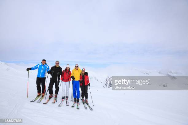 amateur winter sports  alpine skiing. group of skiers. best friends men and women, snow skiers, enjoying  skiing.  high mountain snowy landscape. livigno mountain range, alps. it is located in the italiy. - dolomites stock pictures, royalty-free photos & images