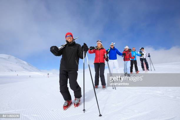 Amateur Winter Sports  alpine skiing. Group of skiers. Best friends men and women, snow skiers carrying skis, enjoying on sunny ski resorts.  High mountain snowy landscape. Livigno mountain range, Alps. It is located in the Italiy.
