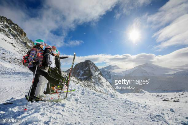 Amateur Winter Sports  alpine skiing. Group of skiers. Best friends men and women, snow skiers  enjoying on sunny ski resorts.  High mountain snowy landscape.  Italian Alps mountain of the Dolomites  Italy, Europe.