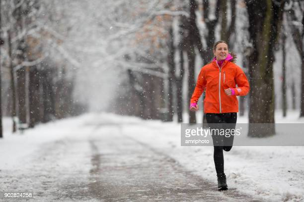 Amateur Winter Sports - happy 43 years old woman jogging in snowfallthrough winter alley