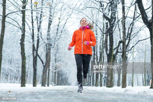Amateur Winter Sports - low perspective sporty woman jogging on country road in winter