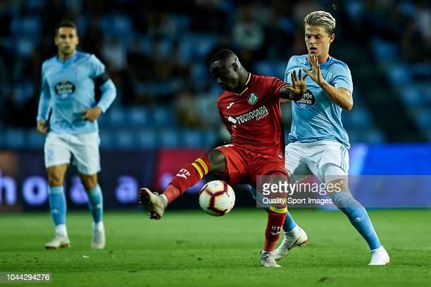 Amath Ndiaye of Getafe CF is challenged by Mathias Jensen of Celta de Vigo during the La Liga match between RC Celta de Vigo and Getafe CF at Estadio...