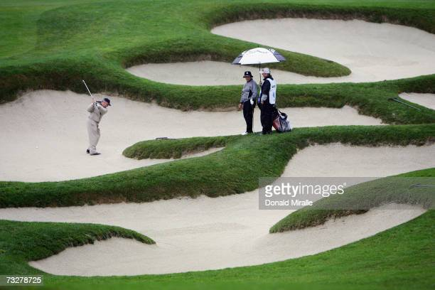Amatuer John Scarpa hits out of the bunker on the 11th hole as Omar Uresti and caddie watch during the 2nd round of the AT&T Pebble Beach National...