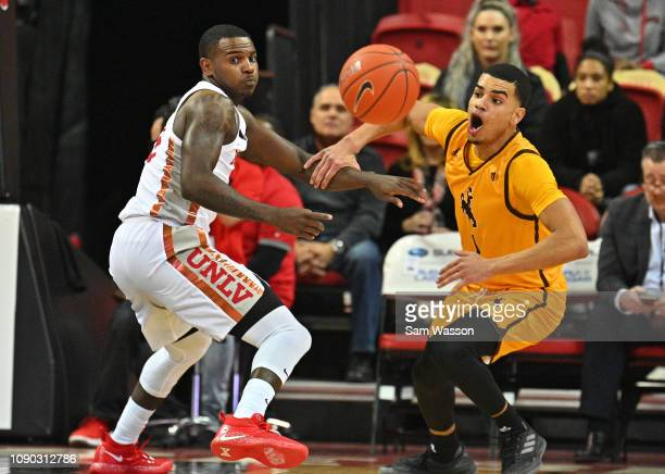 Amauri Hardy of the UNLV Rebels and Justin James of the Wyoming Cowboys chase after a loose ball during their game at the Thomas Mack Center on...