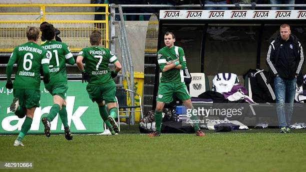 Amaury Bischoff of Muenster celebrates with team mates after scoring the opening goal from a freekick as head coach Maik Walpurgis of Osnabrueck...