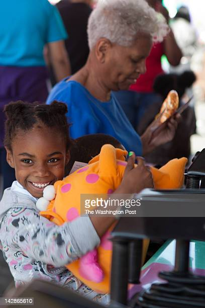 Amaya Quarles hugs a stuffed animal won for her by her grandmother Lois Davis in a racing game at the fairWarm weather welcomed the 2012 opening of...