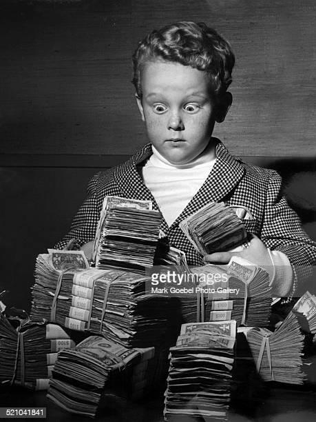 Amazed boy with bundle of cash, late 1960s.