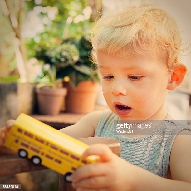 Amazed little boy looking at toy bus