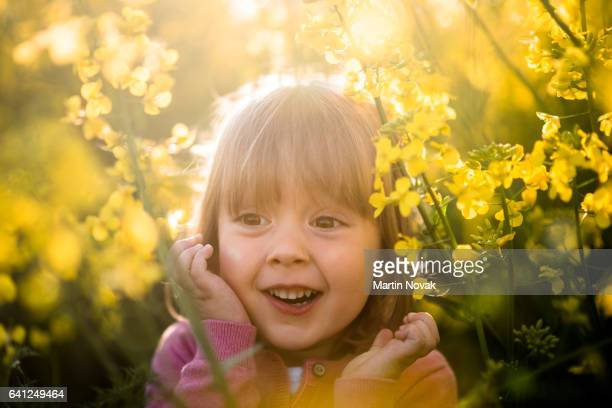 Amazed little girl surrounded by rapeseed flowers