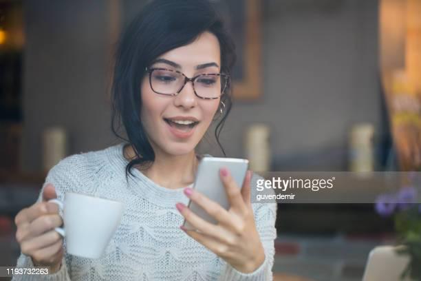 verbaasd vrouw controleren telefoon vinden goed nieuws - vinden stockfoto's en -beelden