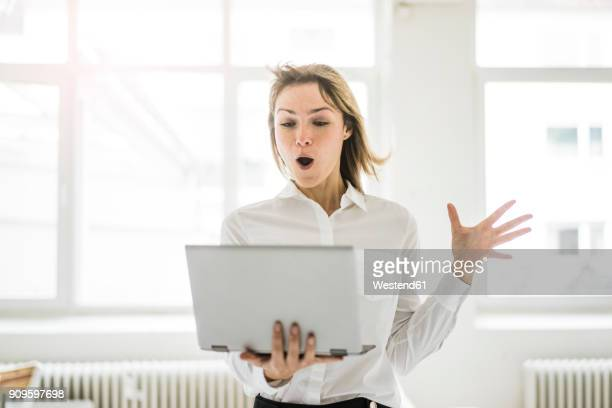 amazed woman holding laptop - internet stock-fotos und bilder