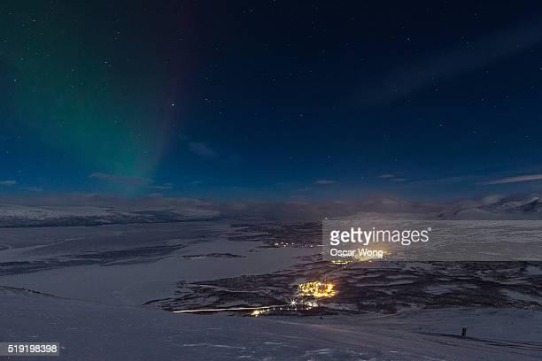 Amazing aurora borealis over town by lake