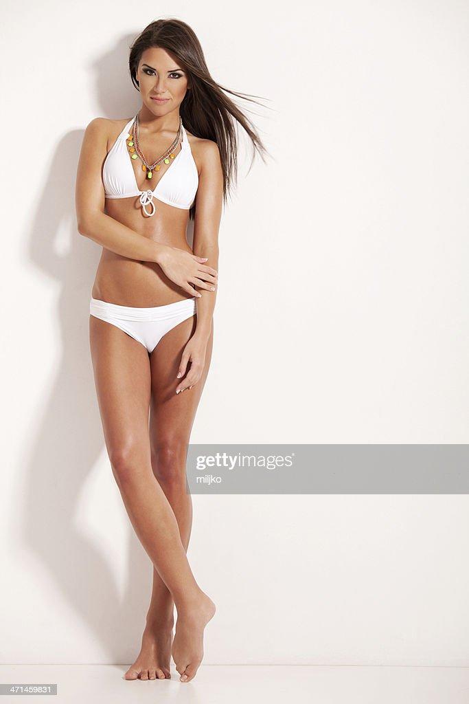 Amazing brunette posing in white bikini : Stock Photo