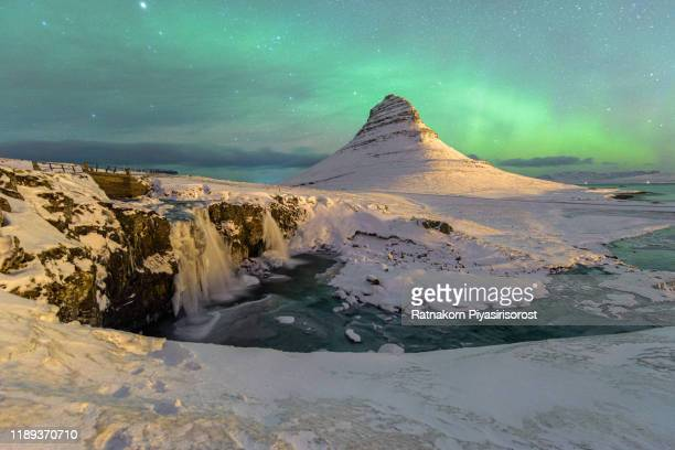 amazing celestial lights of aurora borealis with mountain kirjuffell in iceland at winter - tundra stock pictures, royalty-free photos & images