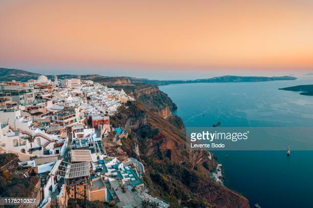 amazing evening view of fira, caldera, volcano of santorini, greece with cruise ships at sunset. cloudy dramatic sky - caldera stock pictures, royalty-free photos & images