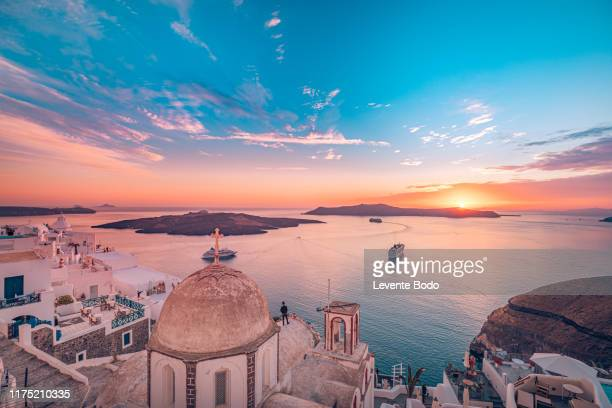 amazing evening view of fira, caldera, volcano of santorini, greece with cruise ships at sunset. cloudy dramatic sky - kreuzfahrtschiff stock-fotos und bilder