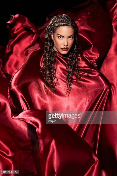 amazing fashion model posing in red satin dress - satin dress stock photos and pictures