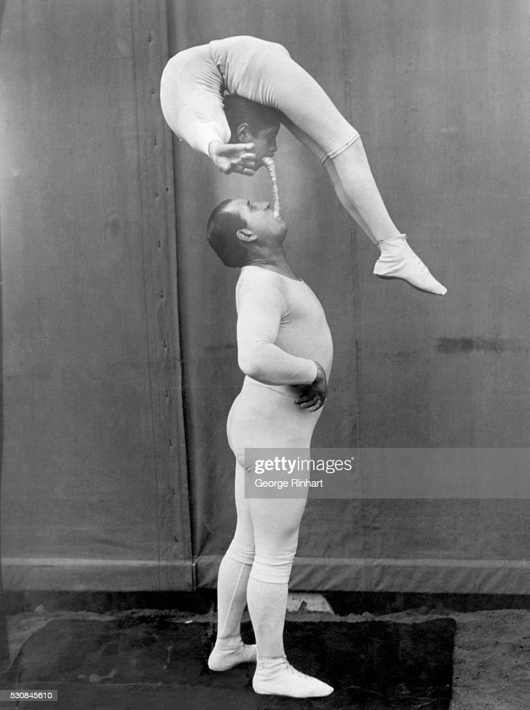 Amazing feat of strength, balance, and flexibility is exhibited by this pair of circus acrobats/contortionists. Undated photograph.