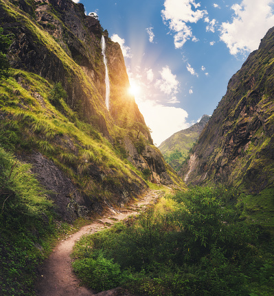 Amazing Himalayan mountains covered green grass, high waterfall, beautiful path, green trees, blue sky with yellow sun and clouds in Nepal at sunset. Mountain canyon. Travel in Himalayas.Landscape 924170590