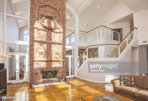 amazing home interior with brick fireplace and spectacular glass staircase. - ceiling stock pictures, royalty-free photos & images