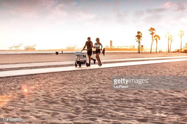 amazing modern and young family running on the beach at sunset - long beach california stock pictures, royalty-free photos & images
