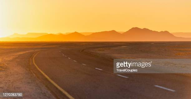 amazing sunlight near monument valley, arizona, usa. view of historic u.s. route 163 running through famous monument valley in beautiful golden evening light at sunset on a beautiful sunny day with blue sky in summer, utah, usa - national landmark stock pictures, royalty-free photos & images
