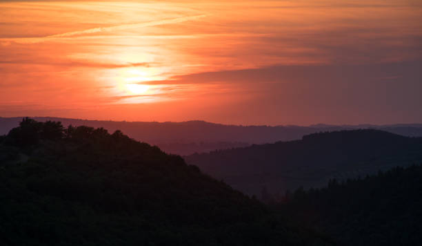 amazing sunrise or sunset in the mountains of Tuscani, Italy. The orange sun is shining across the grey clouds and lighting the dark valleys and mountains. Horizontal photo