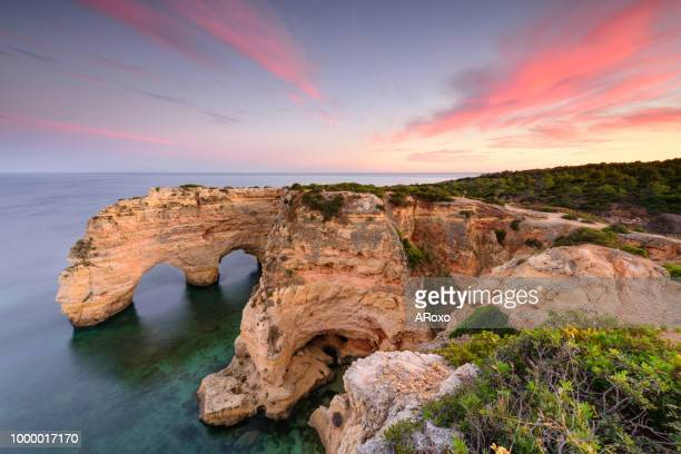 amazing sunset at marinha beach in the algarve, portugal. summer tourist attraction. - faro city portugal stock photos and pictures
