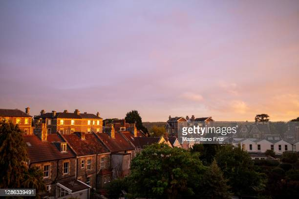 amazing sunset with vibrant pink and yellow colours over the house rooftop of the city of bristol, uk - bristol england stock pictures, royalty-free photos & images