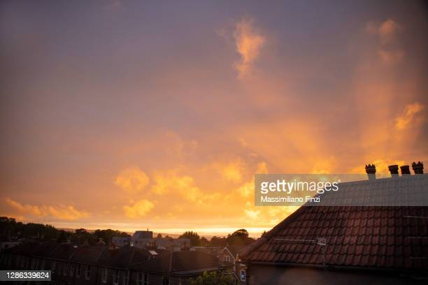 amazing sunset with vibrant pink and yellow colours over the house rooftop of the city of bristol, uk - sunset stock pictures, royalty-free photos & images