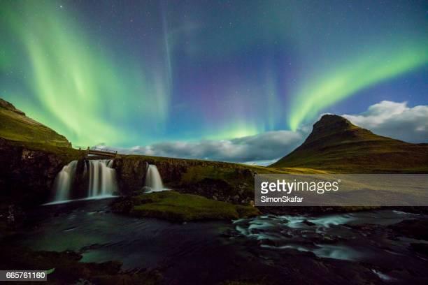 Amazing view of Aurora Borealis over waterfall
