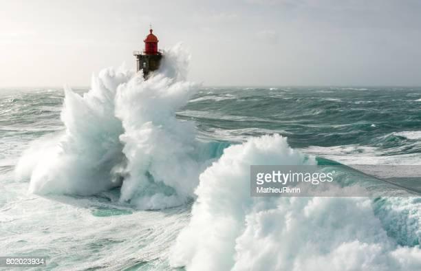 amazing wave on la jument lighthouse - leuchtturm sturm stock-fotos und bilder