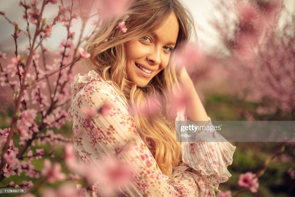 Amazing young woman posing in apricot tree orchard at spring : Stock Photo