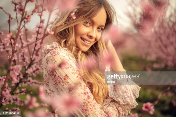 amazing young woman posing in apricot tree orchard at spring - moda imagens e fotografias de stock