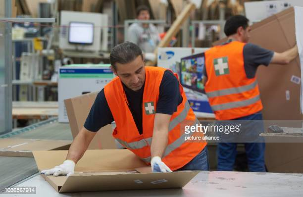 Amazon employees Oktay Kuecuek and Hasan Katirici at the packaging department of the Amazon logistics centre in Werne Germany 12 November 2015 The...