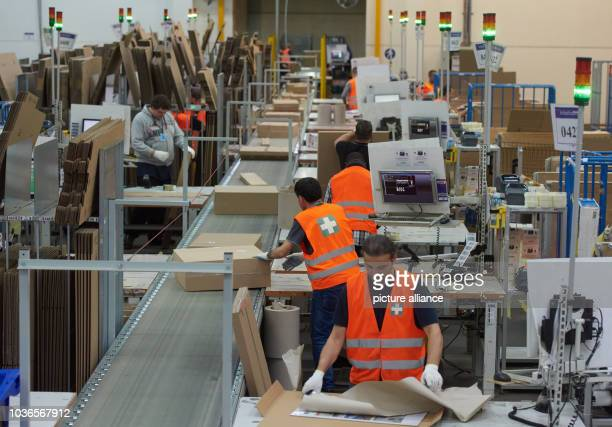 Amazon employees Oktay Kuecuek and Hasan Katirici at work in the packing department of the Amazon logistics centre in Werne Germany 12 November 2015...