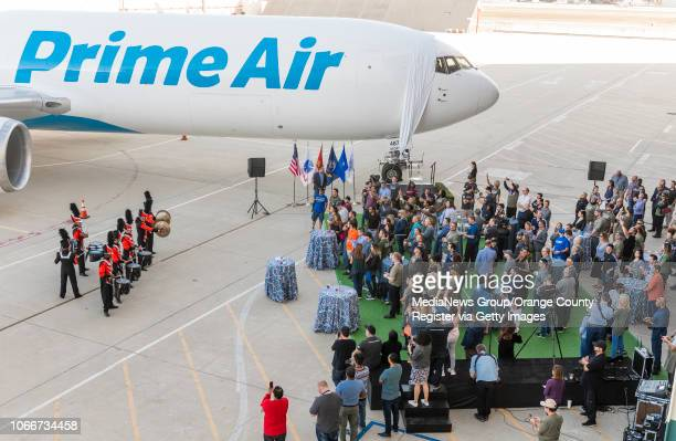 Amazon employees that are military veterans and spouses of veterans listen to a drumming group during next to the company's latest airplane during an...