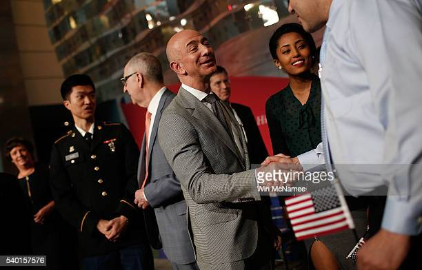 Amazon Founder and Washington Post owner Jeff Bezos greets newly naturalized US citizens during a naturalization ceremony on the 100th anniversary of...