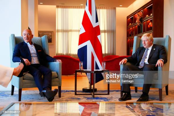 Amazon founder Jeff Bezos and British Prime Minister Boris Johnson watch as Lauren Sánchez shows off her shoes during a meeting at the UK diplomatic...