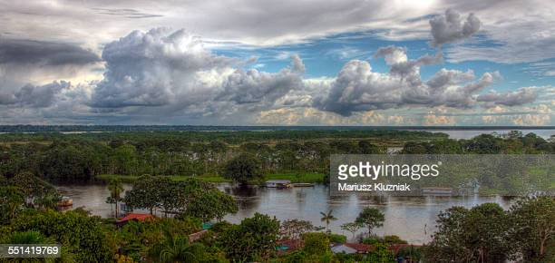 Amazon river shores, floating houses and clouds