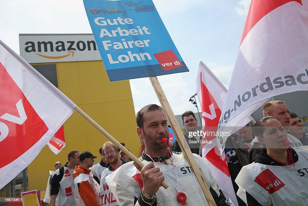 Amazon workers wearing bibs of the ver.di service industry labour union blow into whistles while striking outside the Amazon warehouse on May 14, 2013 in Leipzig, Germany. Approximately 5,000 Amazon workers at the Leipzig and Bad Hersfeld warehouses have gone on a 24-hour strike in an effort to press the company harder in their ongoing labour dispute over wages and work hours.