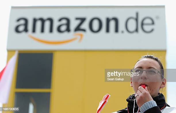 Amazon workers wearing bibs of the verdi service industry labour union blow into whistles while striking outside the Amazon warehouse on May 14 2013...