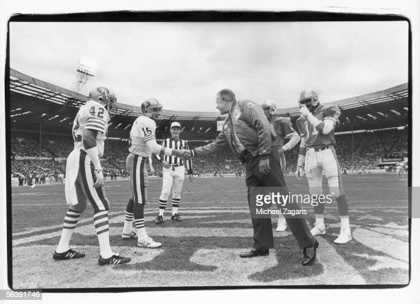 Ambassador Charles Price shakes hands with quarterback Joe Montana of the San Francisco 49ers before the 1988 American Bowl game against the Miami...