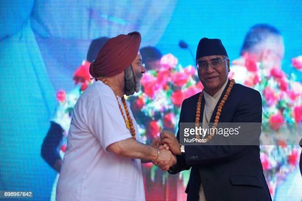 Ambassador of India to Nepal Manjeev Singh Puri and Prime Minister of Nepal Sher Bahadur Deuba hand shake after the celebration of International Day...