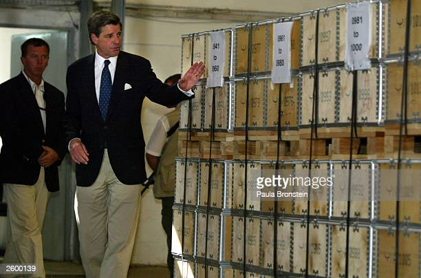 Ambassador Paul Bremer tours a distribution warehouse along with other officials full of cases with new Iraqi dinar banknotes which were introduced...