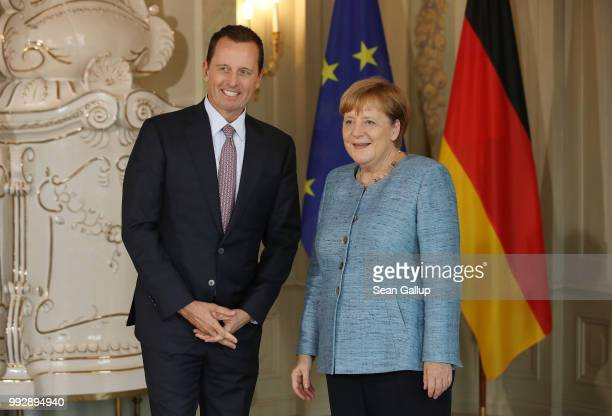 S Ambassador Richard Grenell poses for a photo with German Chancellor Angela Merkel upon his arrival at a reception for the diplomatic corps hosted...