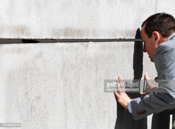 US Ambassador to Berlin Richard Grenell looks through a gap between the wall parts on the grounds of the Berlin Wall Memorial in the Bernauer street...