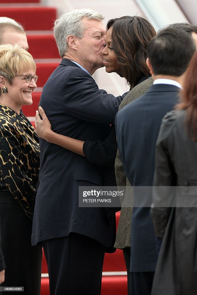 US Ambassador to China Max Baucus (C-L) kisses US First Lady Michelle Obama (C-R) before she departs Chengdu Shuangliu airport in China's southwest Sichuan province for the US on March 26, 2014. Michelle Obama arrived in China on March 20 with her mother and daughters when they kicked off a seven-day, three-city tour where she focused on education and cultural exchange. AFP PHOTO/Peter PARKS