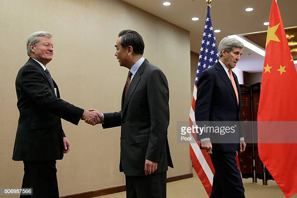 S Ambassador to China Max Baucus shakes hands with Chinese Foreign Minister Wang Yi as US Secretary of State John Kerry walks by before a bilateral...