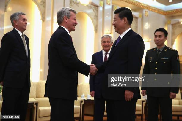 S Ambassador to China Max Baucus shakes hands with Chinese President Xi Jinping as Secretary of Defense Chuck Hagel looks on during a meeting at the...